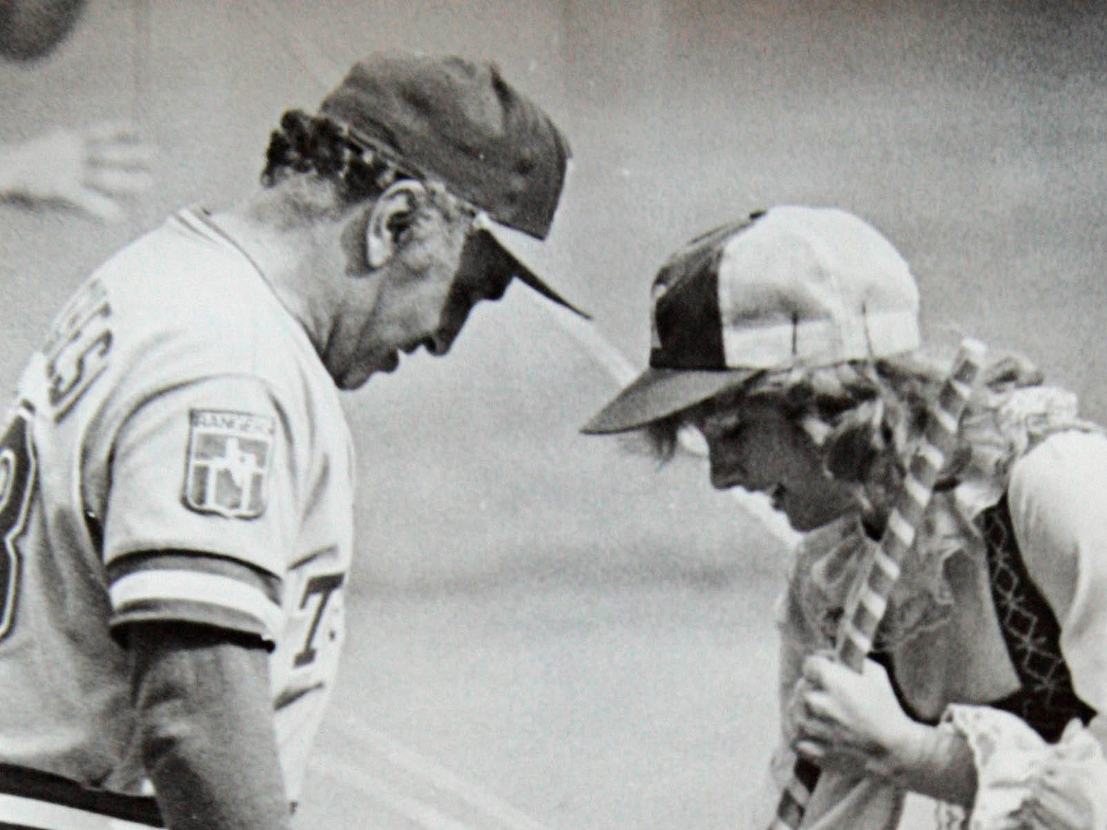 Anne Haines aka Bonnie Brewer, sweeps the dirt off the shoes of a third base coach for the Texas Rangers during a game at County Stadium in 1979.