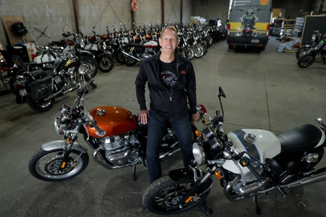 Rod Copes, president of the Royal Enfield North American division, sits on a Royal Enfield INT 650 twin, next to a Continental GT 650 twin, both new models, at the company's warehouse on East Pittsburgh Avenue in Milwaukee last week.