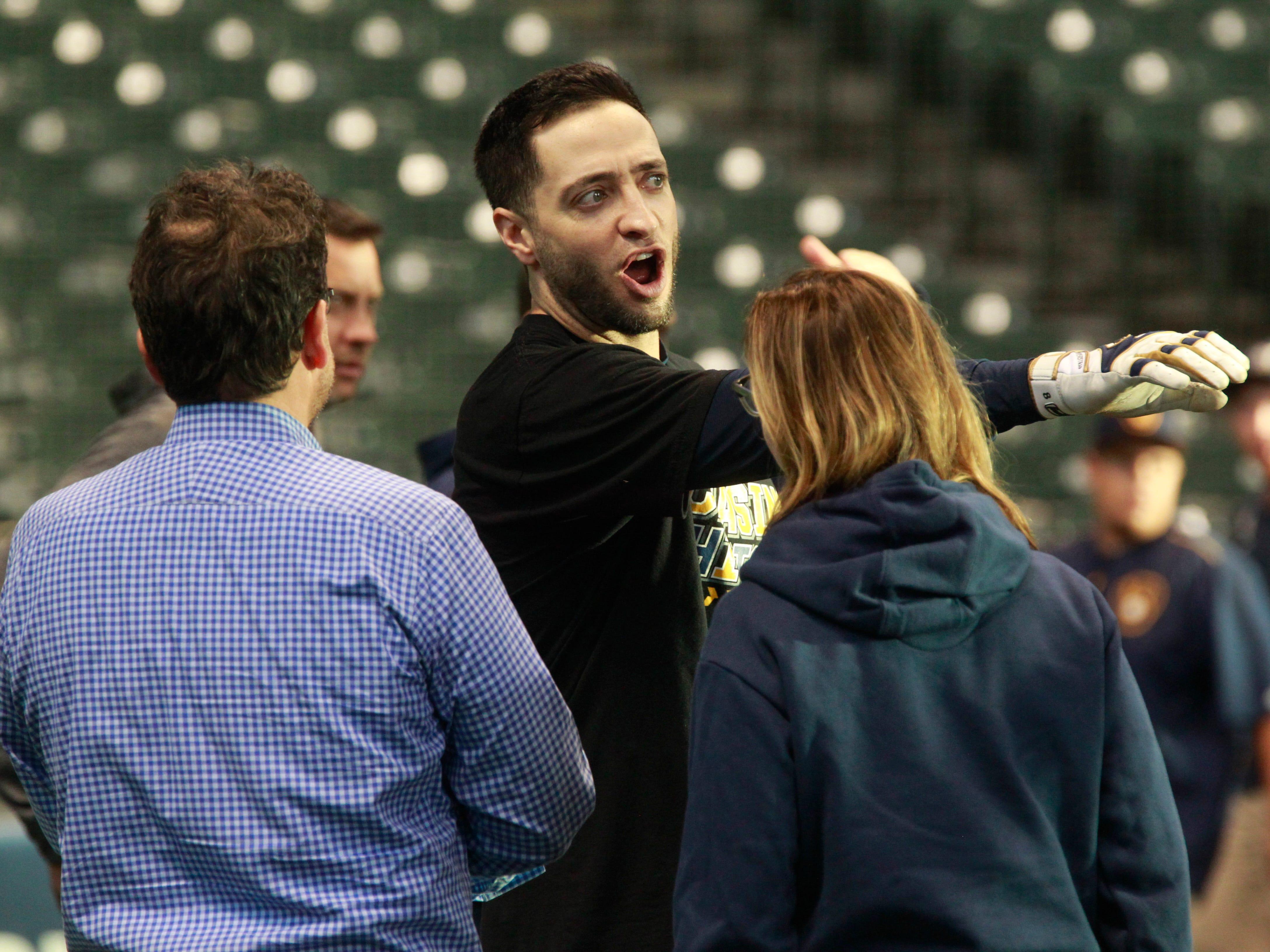 Brewers veteran outfielder Ryan Braun talks with team owner Mark Attanasio (left) during practice on Wednesday at Miller Park.