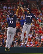 Brewers leftfielder Ryan Braun leaps to celebrate with third base coach Ed Sedar after hitting a solo home run against the Cardinals on Sept. 24.