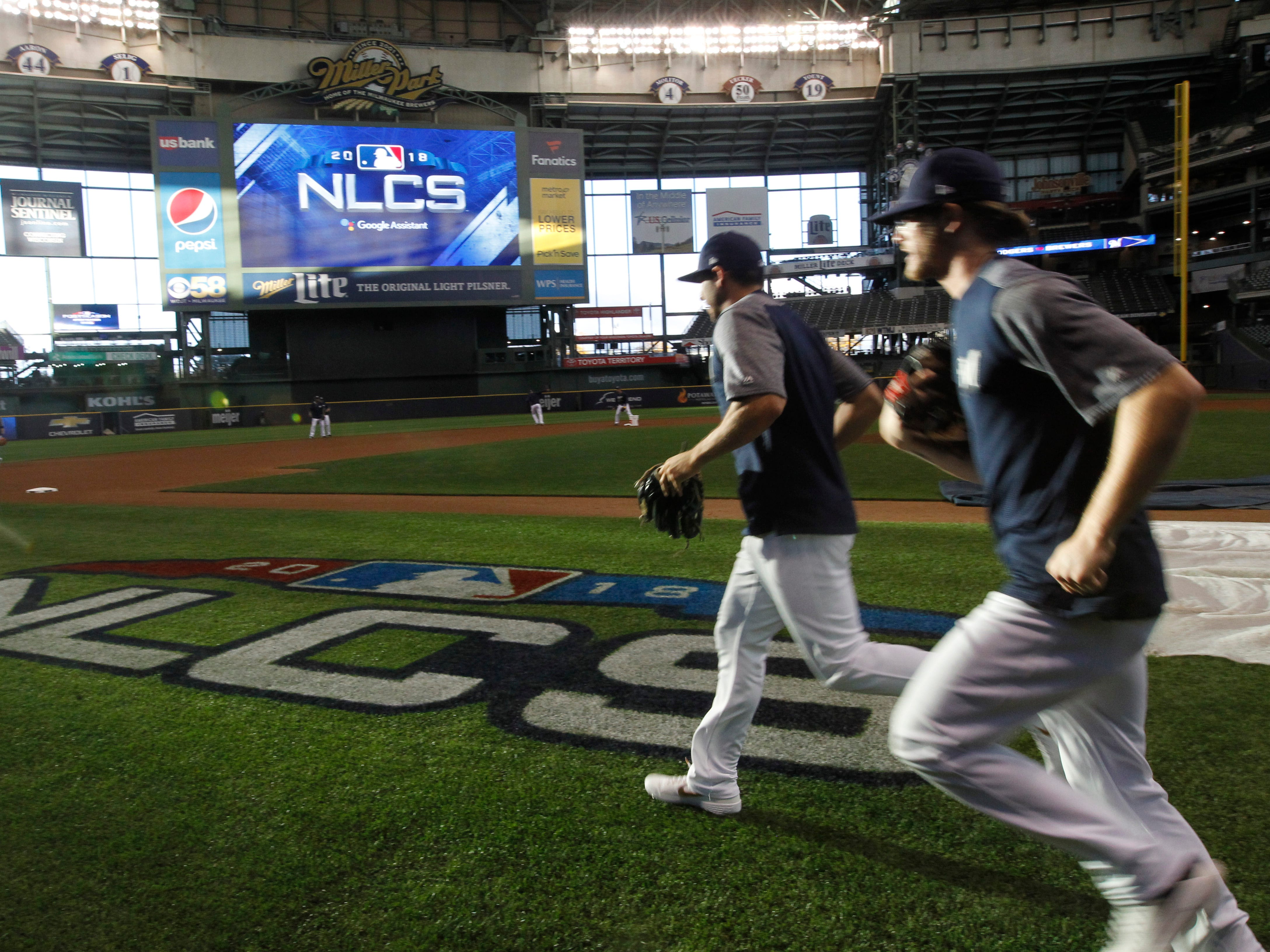 Brewers players run  pass a newly painted NLCS sign on the field during practice on Wednesday at Miller Park.