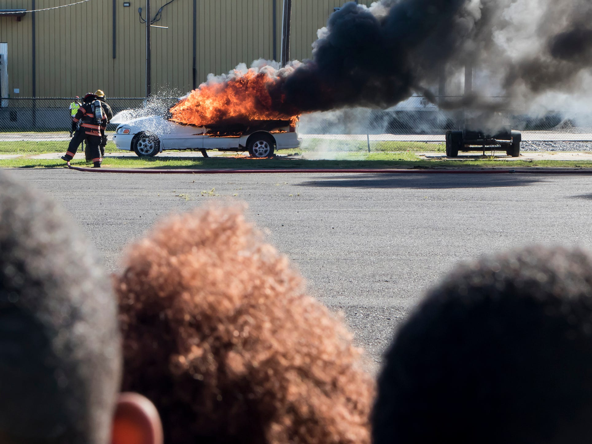 Children watch as Monroe firefighters work to extinguish a flaming car during a fire prevention week demonstration held in Monroe, La. on Oct. 11.