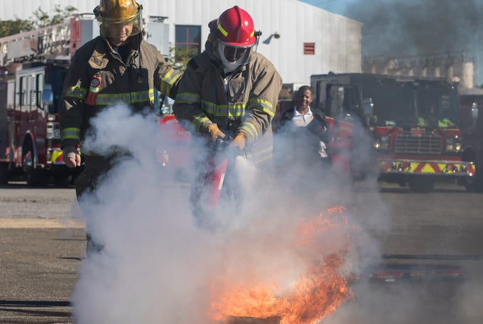 Monroe firefighter, Landon Telano, left, guides Minnie Ruffin Elementary School teacher Nick Harrison in using a fire extinguisher to put out a fire in front of a group of area grade school children during a fire prevention week demonstration held in Monroe, La. on Oct. 11.