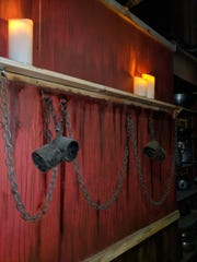 Shackles hang from the walls of a dimly-lit hallway that leads to each escape room.