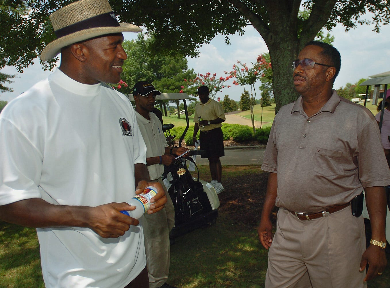 Four-time Heavyweight Champion Evander Holyfield, left, talks with Greg Calhoun while participating in the Greg Calhoun Golf Tournament Monday, June 26, 2006 at Capitol Hill Golf Course in Prattville, Ala. (Montgomery Advertiser, Karen S. Doerr)