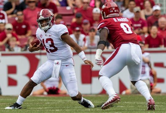 Alabama quarterback Tua Tagovailoa (13) carries against Arkansas linebacker De'Jon Harris (8) during first half action in Fayetteville, Ark., on Saturday October 6, 2018.