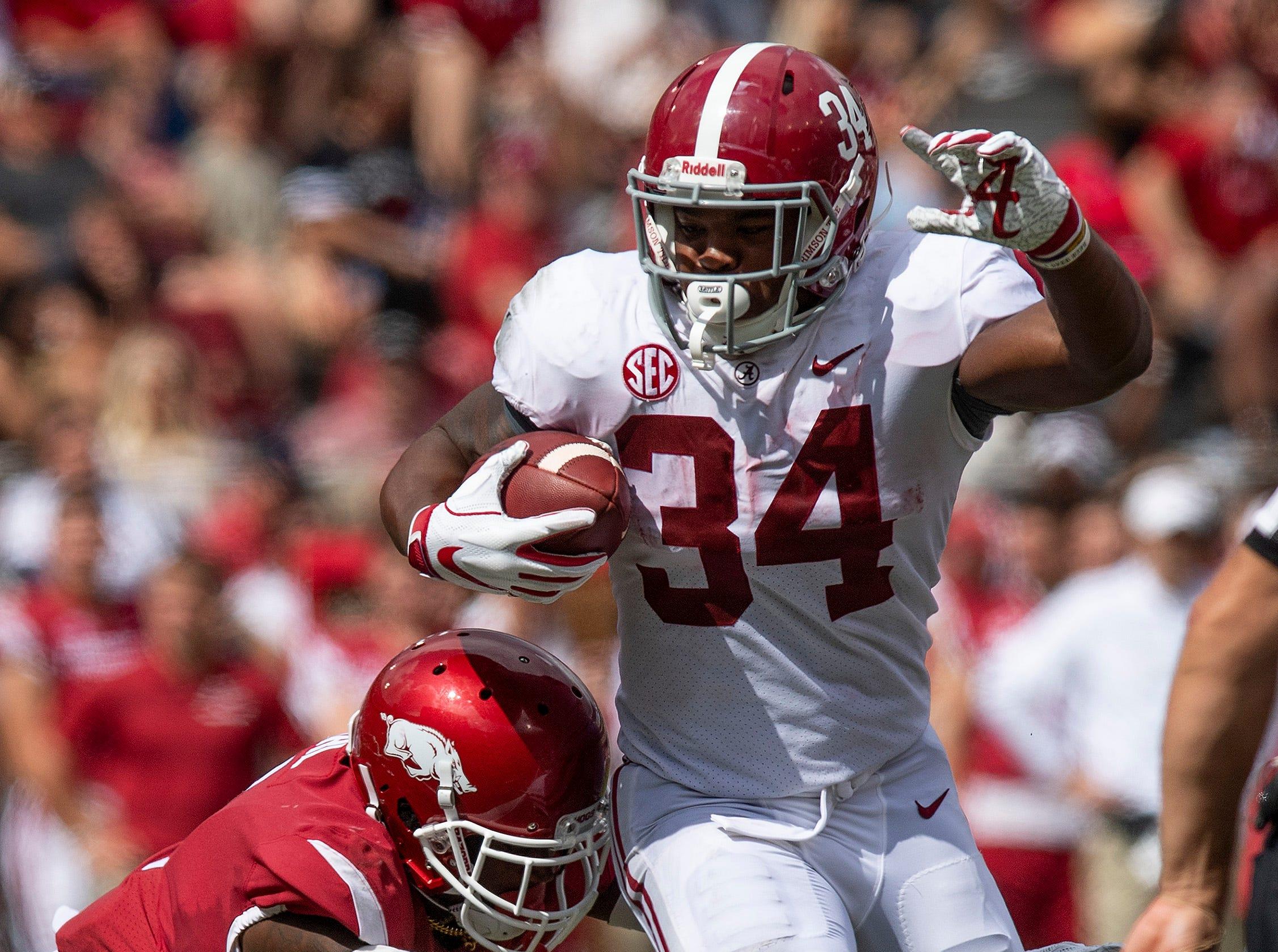 Alabama running back Damien Harris (34) is hit by Arkansas defensive back Kamren Curl (2) during second half action in Fayetteville, Ark., on Saturday October 6, 2018.