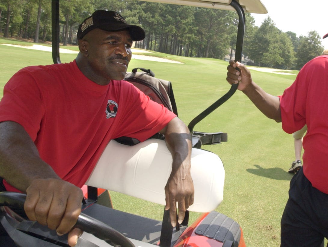 Evander Holyfield, left, speaks with Greg Calhoun during the Sickle Cell Foundation Benefit Golf Tournament at Wynlakes Golf and Country Club in Montgomery, Ala., July 25, 2005.  (Rainier Ehrhardt/Special to the Advertiser)