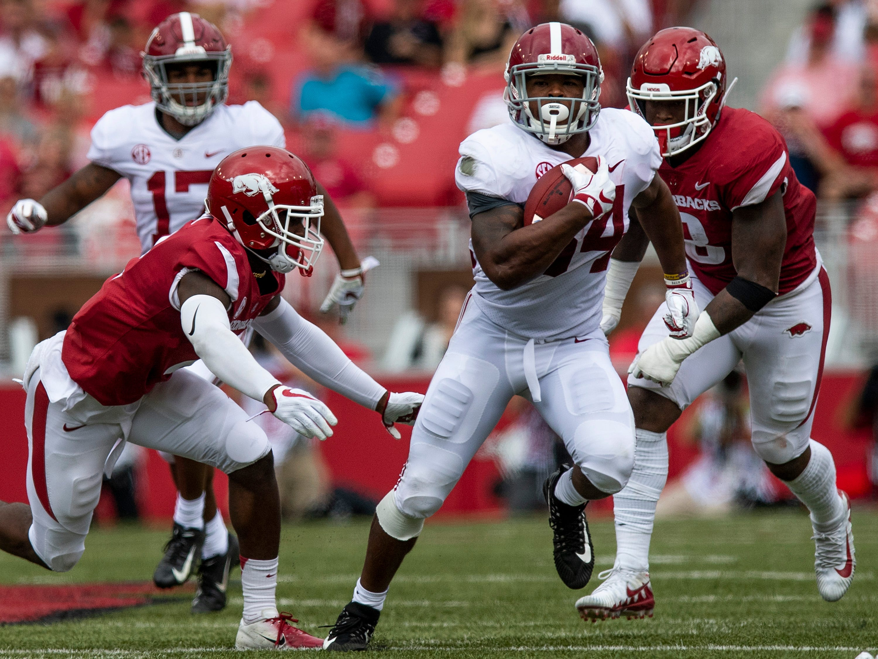 Alabama running back Damien Harris (34) eludes tackles against Arkansas during first half action in Fayetteville, Ark., on Saturday October 6, 2018.