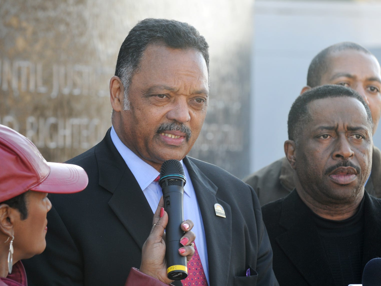 March 8 - - Jesse Jackson stopped at the Civil Rights Memorial to speak of the legacy of Martin Luther King on Saturday, March 8, 2008, in Montgomery, Ala.. At left, Cubie Rae Hayes, Calhoun Enterprises PR director holds a microphone, at right, Greg Calhoun and Jon Dow. (Montgomery Advertiser, Lloyd Gallman)