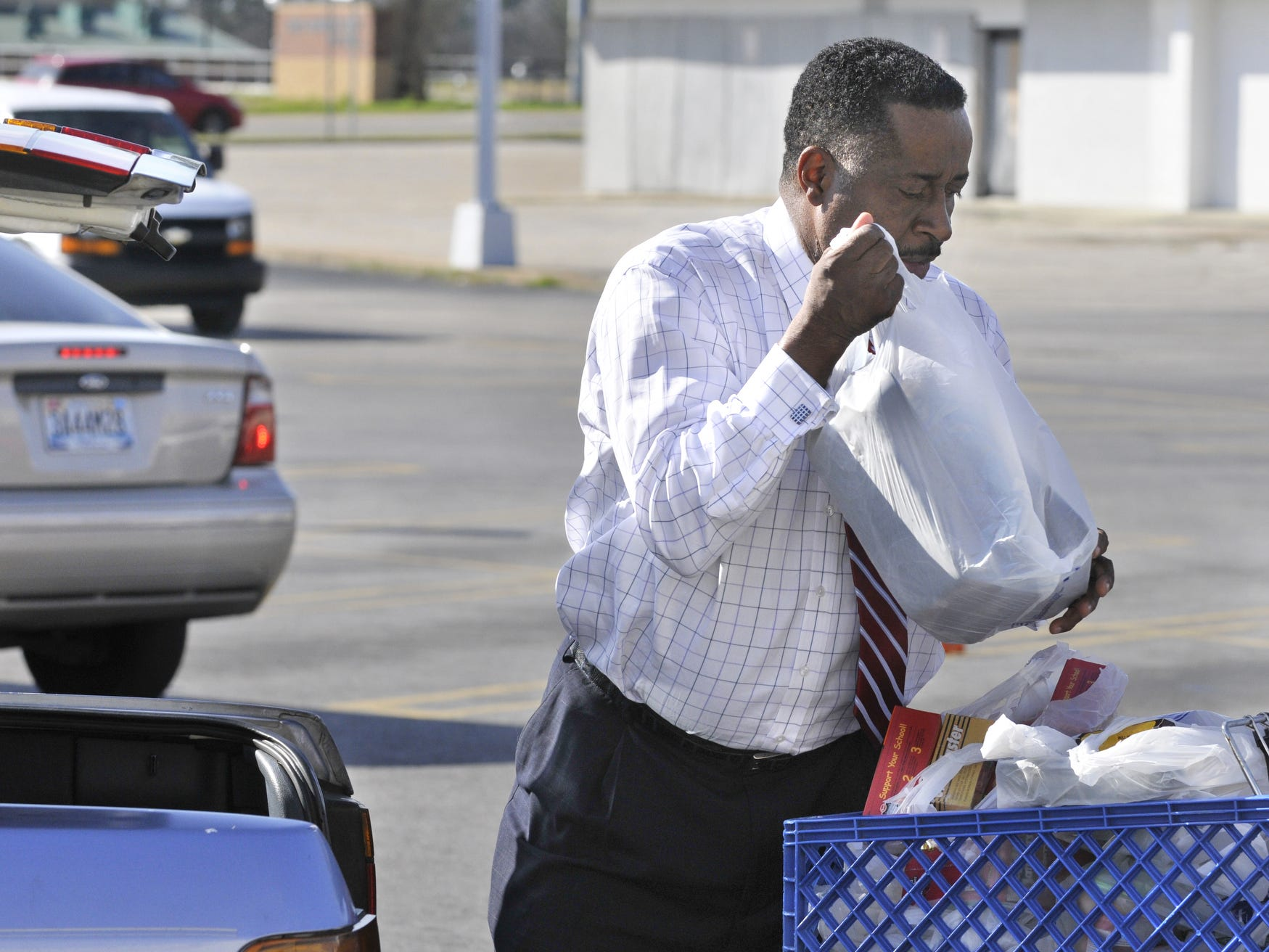 Greg Calhoun puts groceries in the trunk of a customer's car at his Calhoun Foods store on Fairview Avenue in Montgomery, Ala. on Wednesday, Feb. 8, 2012. (Montgomery Advertiser, Lloyd Gallman)