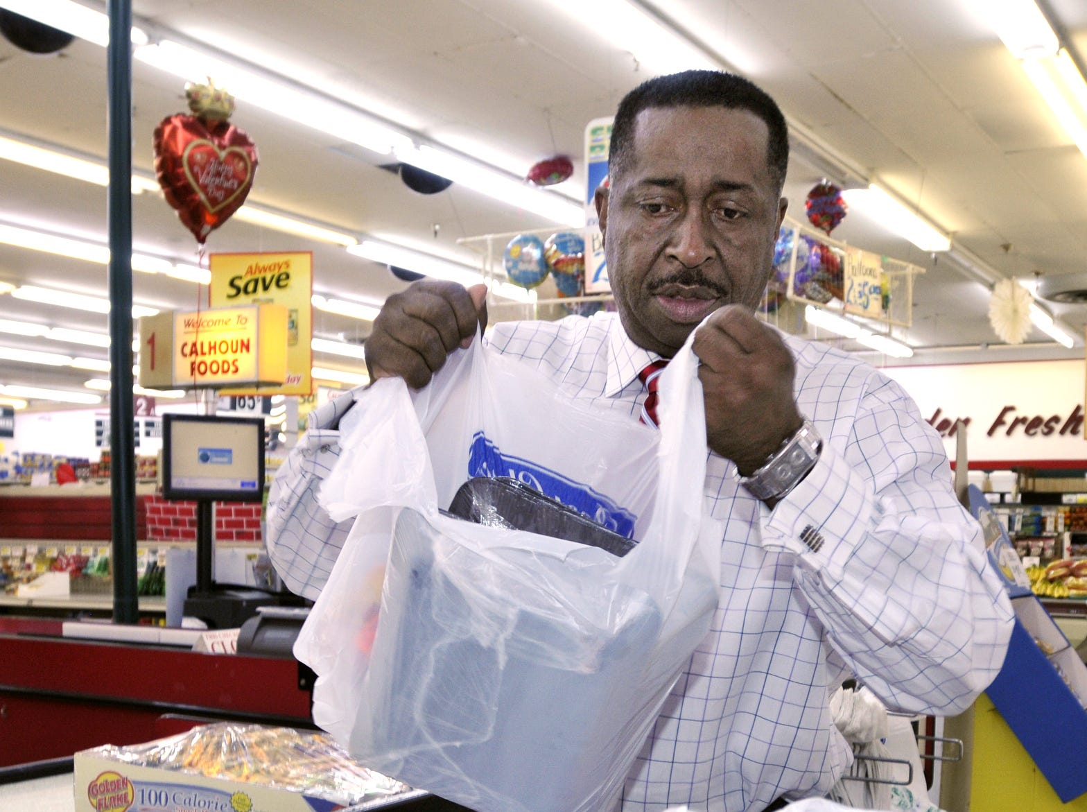 Greg Calhoun bags groceries for a customer at his Calhoun Foods store on Fairview Avenue in Montgomery, Ala. on Wednesday, Feb. 8, 2012. (Montgomery Advertiser, Lloyd Gallman)