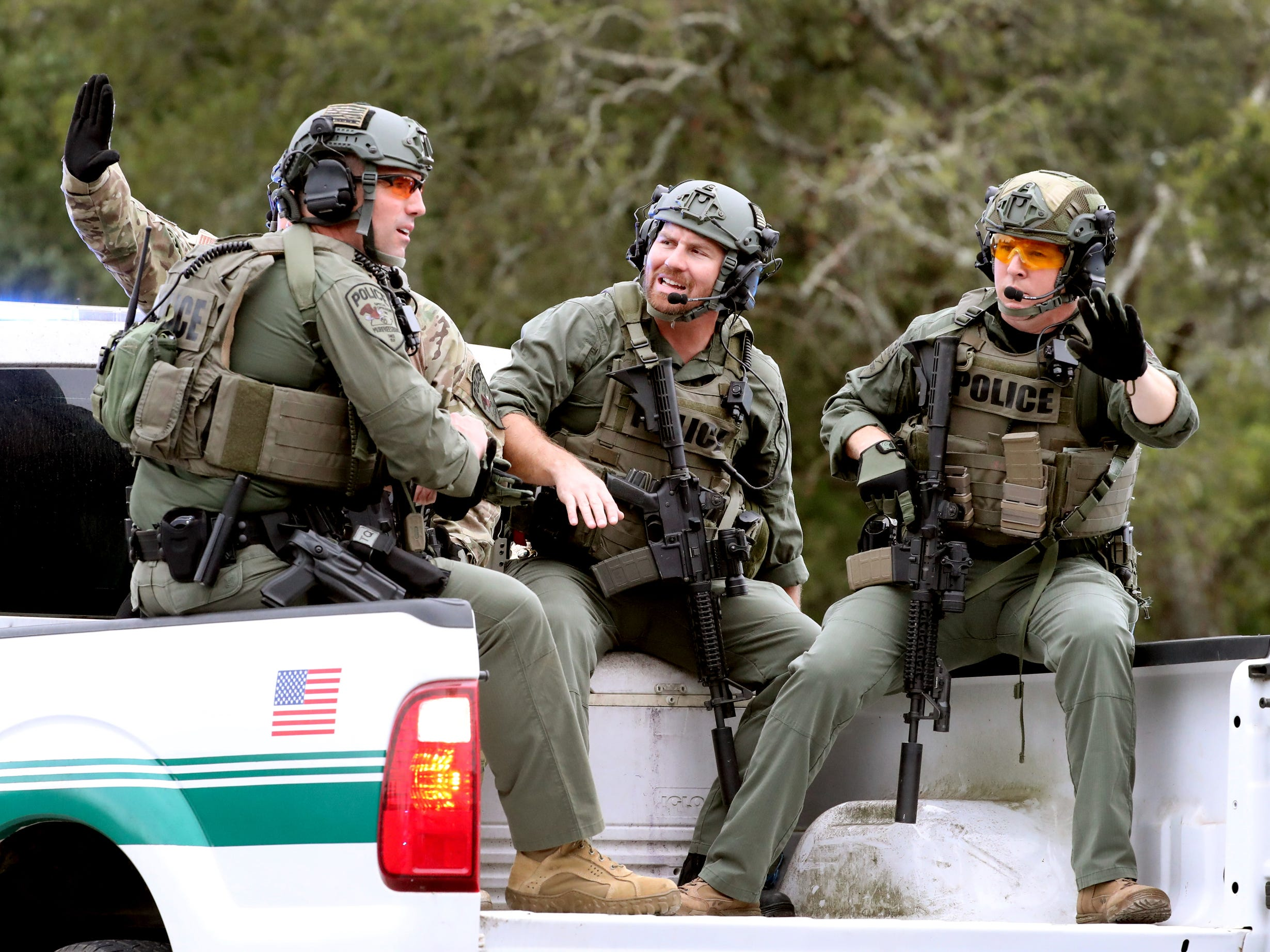Members of law enforcement try to stop traffic from the back of a Rutherford County Sheriff's Department truck as they head to a wooded area to search for two escaped inmates near Old Nashville Highway, and Baker Road Wednesday, Oct. 10, 2018.