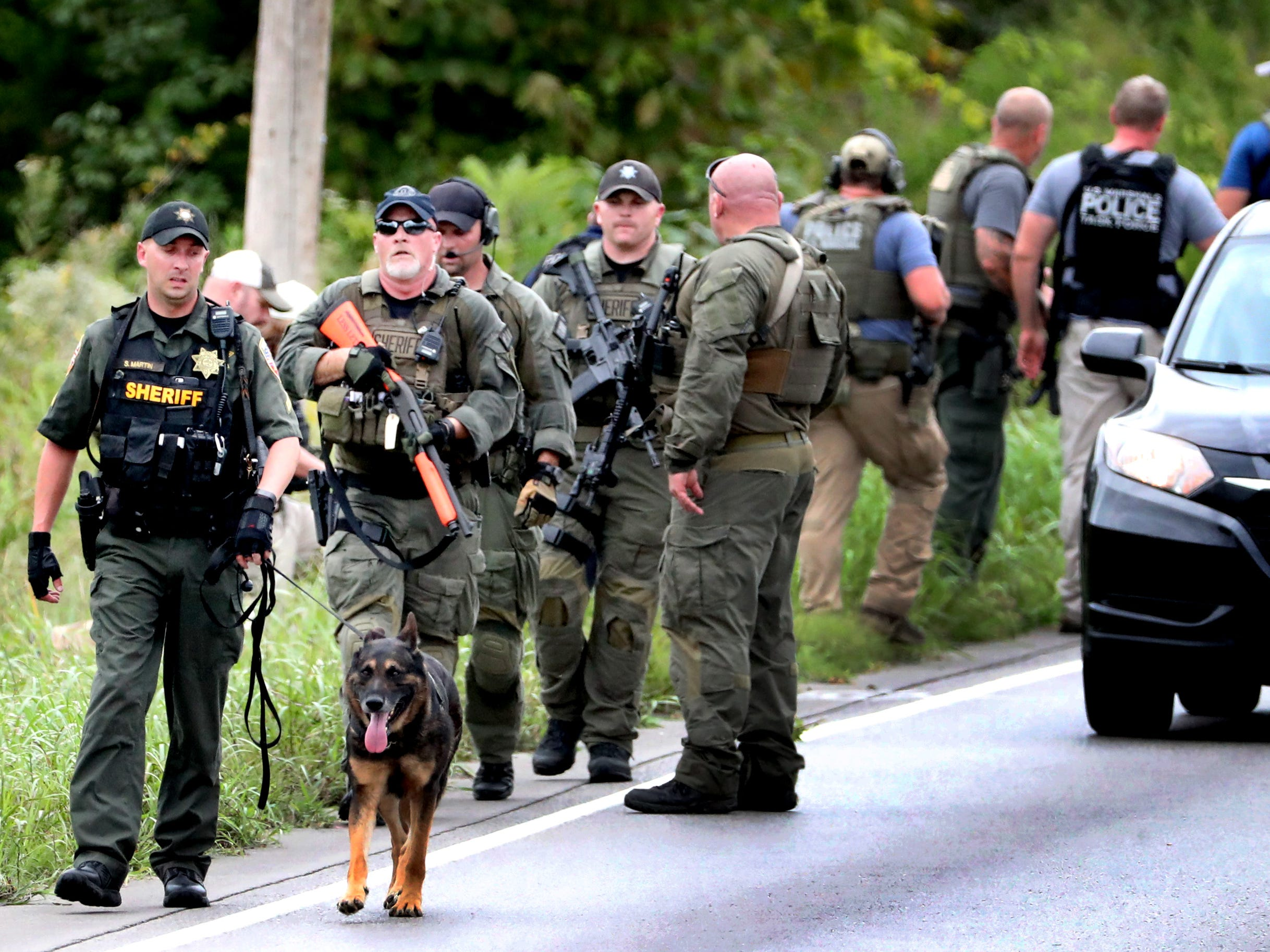 The Rutherford County Sheriff's deputies, and other law enforcement agencies walk along Old Nashville Highway after searching wooded areas for two escaped inmates along Old Nashville Highway near Baker Road Wednesday, Oct. 10, 2018.