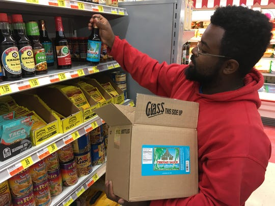 Jr's Foodland employee Javen Sims stocks one of the last remaining boxes of Omni Hut teriyaki sauce.