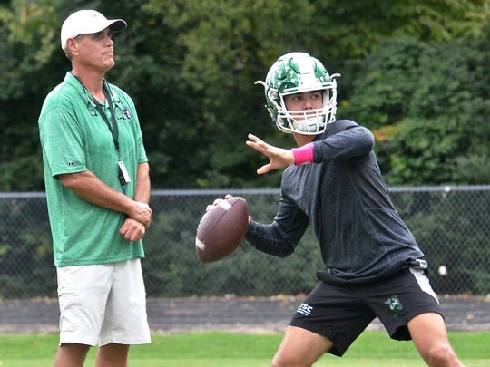 Hillwood coach Kurt Page (left) looks on as his son Hale Page (right) looks to throw downfield.