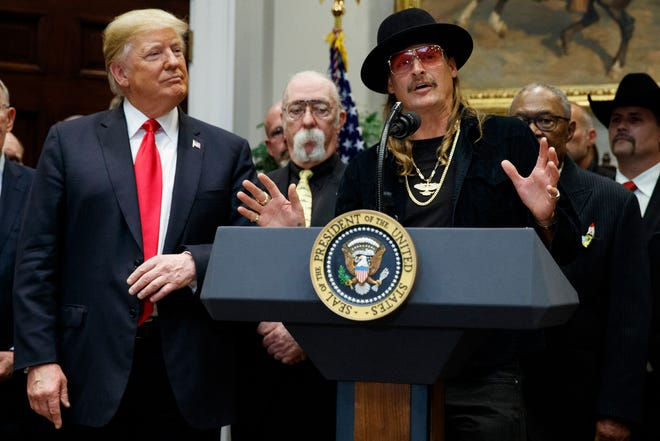 """President Donald Trump looks on as musician Kid Rock speaks during a signing ceremony for the """"Orrin G. Hatch-Bob Goodlatte Music Modernization Act"""" in the Roosevelt Room of the White House on Oct. 11, 2018."""