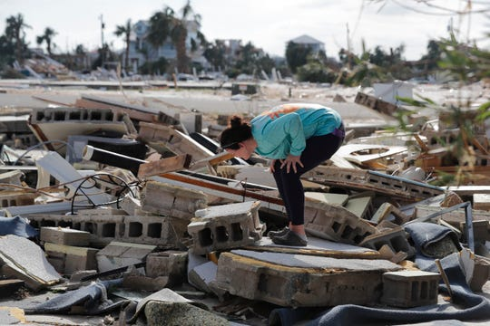 Mishelle McPherson looks for her friend in the rubble of her home Thursday, since she knows the friend stayed behind during Hurricane Michael in Mexico Beach.