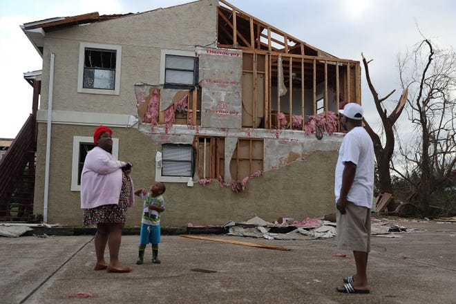 Comeasha Stanley, from left, Ramari Stanley and Terrell Atkinson stand near a heavily damaged apartment Thursday after Hurricane Michael passed through Panama City.