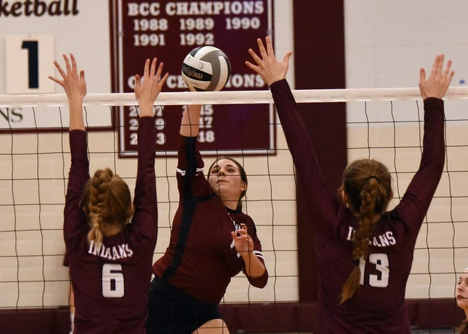 Newark's Gabriella Miller-Barber (center) spikes the ball at Canal Winchester blockers Riley Krueger(left) and Natalie Rarick (right) during a match on Wednesday, Oct. 10, 2018. Newark lost to Canal Winchester in five sets; 25-23, 15-25, 14-25, 25-22, 15-8.
