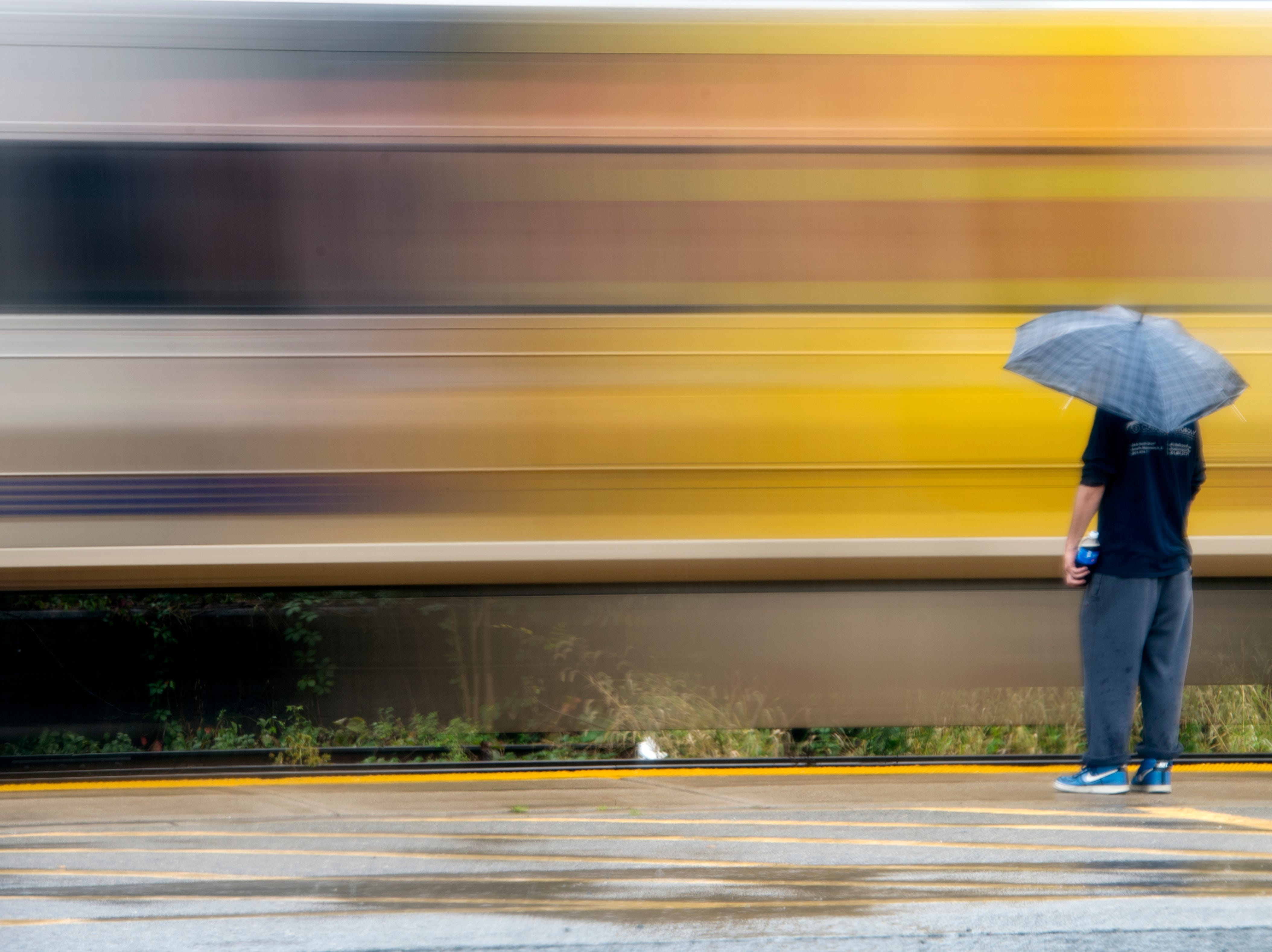 A train passes by as a man waits in the rain with an umbrella at Essex Street Station in Hackensack on Thursday, October 11, 2018.