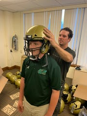 St. Joseph sophomore Zack Reigler has his new helmet custom-fitted by Vicis representative Will Jamieson. The Green Knights took delivery of 150 new Zero1 helmets, given by an anonymous donor, on Thursday.