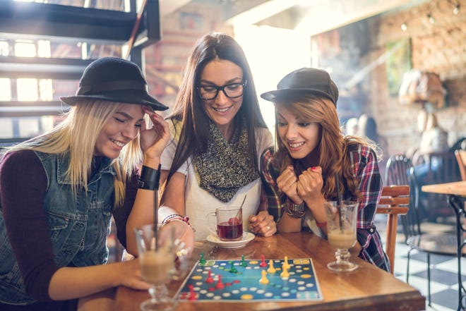 Young smiling women sitting in a cafe and having fun while playing board game.