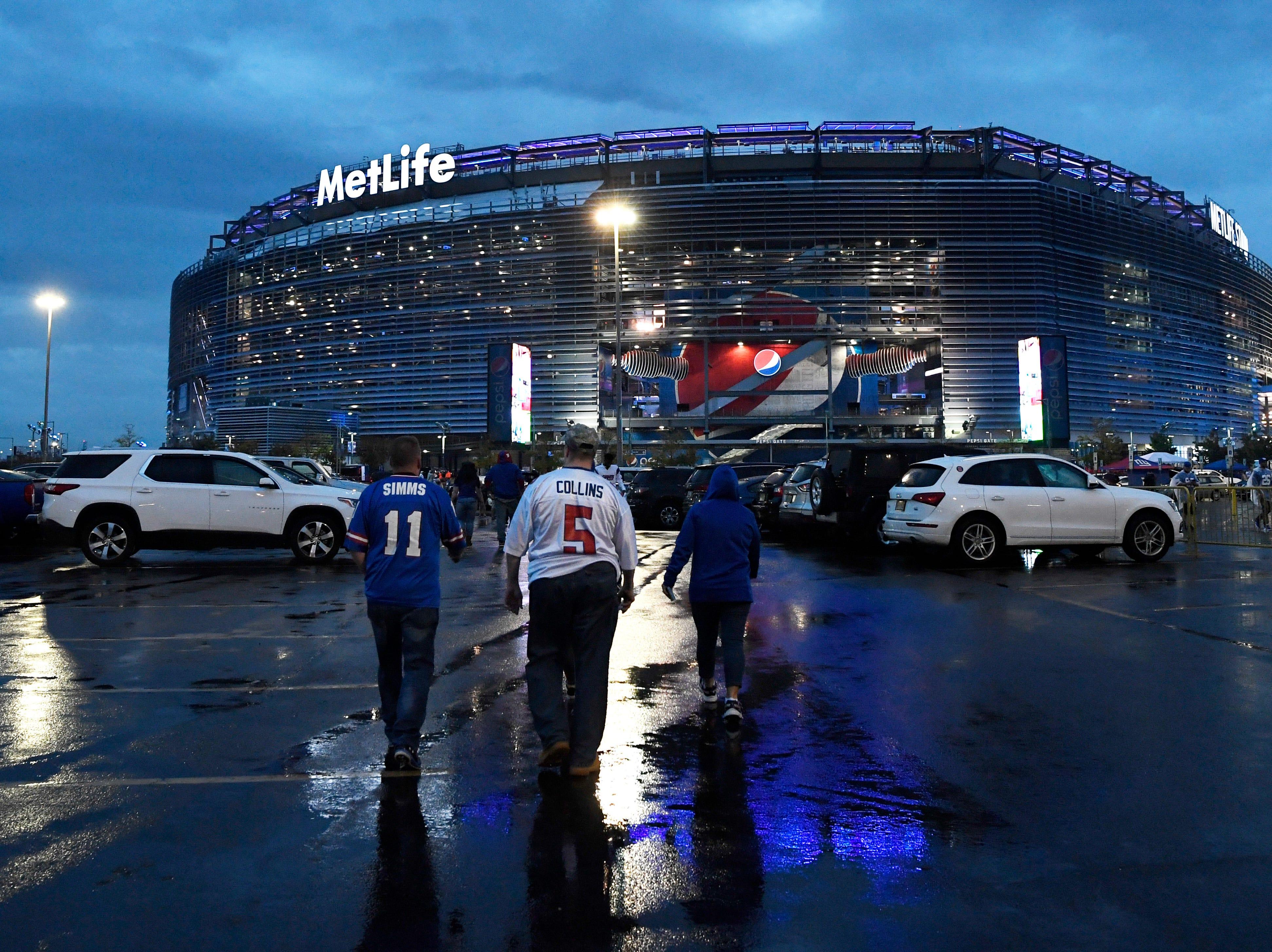 Fans walk across the rainy parking lot of MetLife Stadium before the New York Giants face the Philadelphia Eagles on Thursday, Oct. 11, 2018.