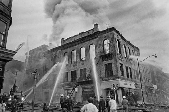 FILE - In this July 15, 1967 file photo, firefighters direct streams of water onto a burning building at the corner of Prince and Court Streets in Newark, N.J., where four days of deadly violence and looting came to be known as the Newark riots.(AP Photo/Marty Lederhandler, File)