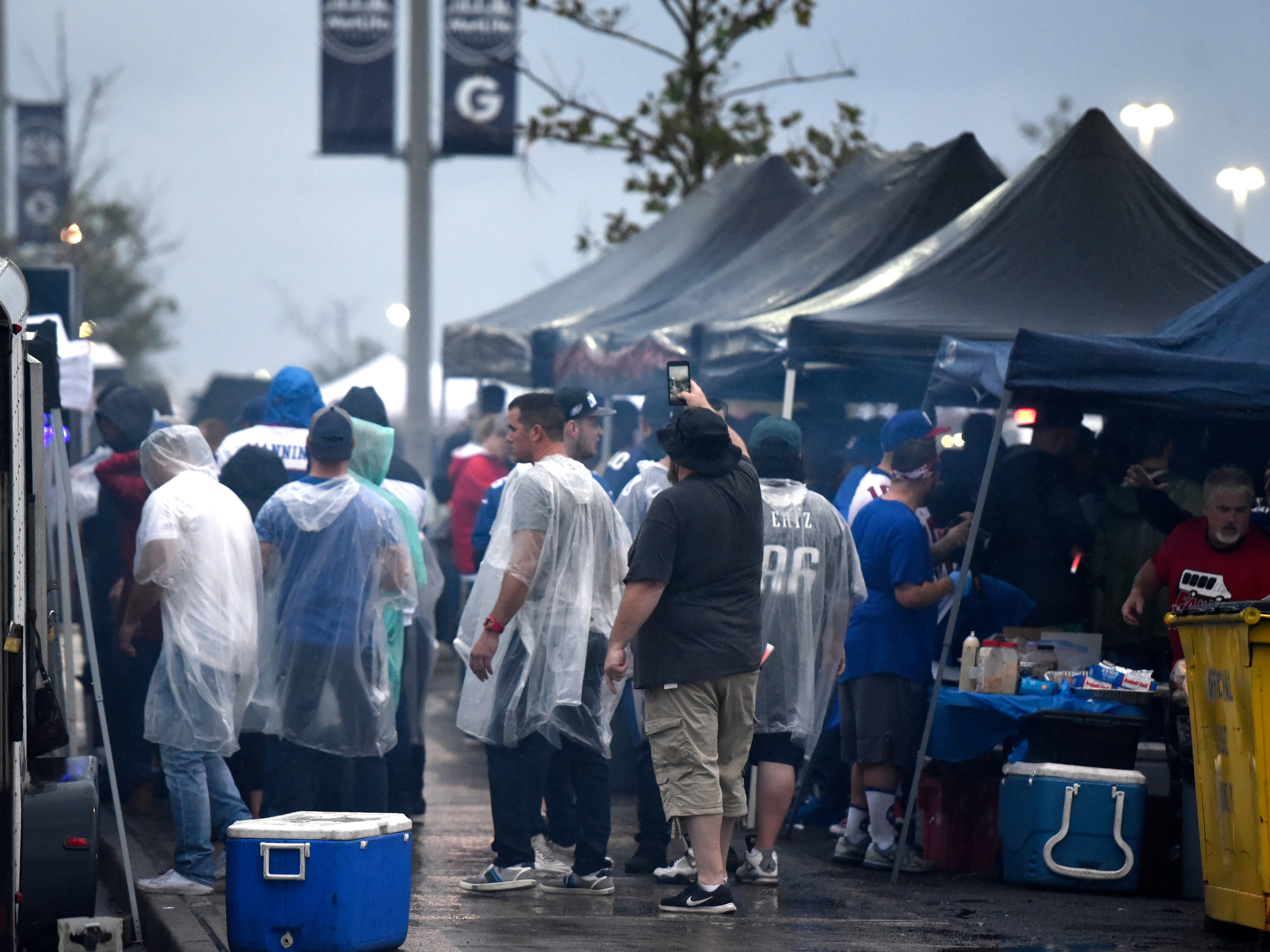 Tailgaters hang out in the rainy parking lot of MetLife Stadium before the New York Giants face the Philadelphia Eagles on Thursday, Oct. 11, 2018.