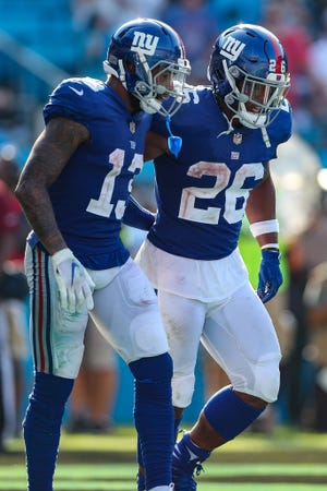 Oct 7, 2018; Charlotte, NC, USA; New York Giants wide receiver Odell Beckham (13) assists running back Saquon Barkley (26) against the Carolina Panthers after Barkley's TD with 1:08 remaining at Bank of America Stadium.