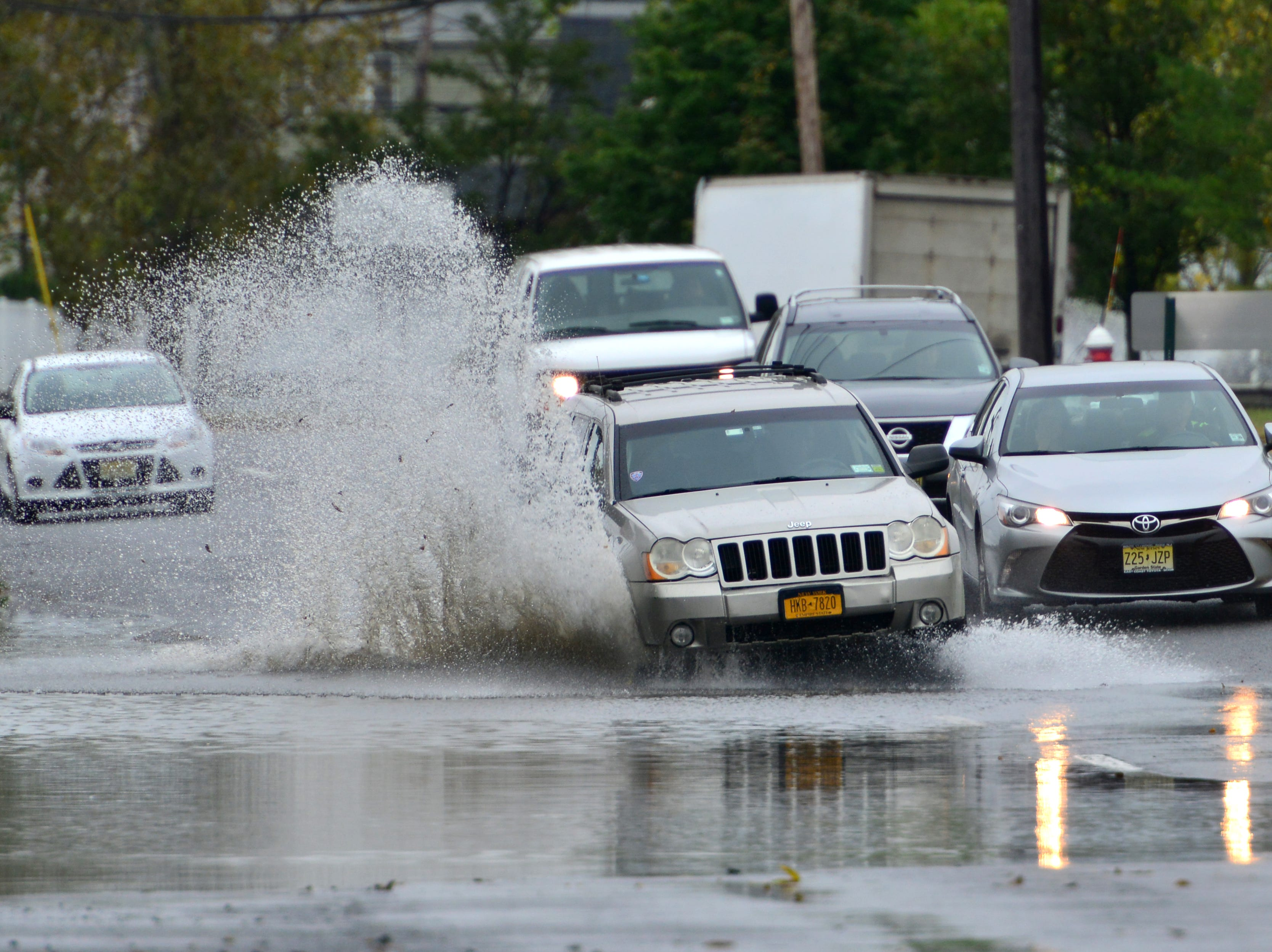 Cars pass through the flooded right lane of River St in Little Ferry on Thursday October 11, 2018.