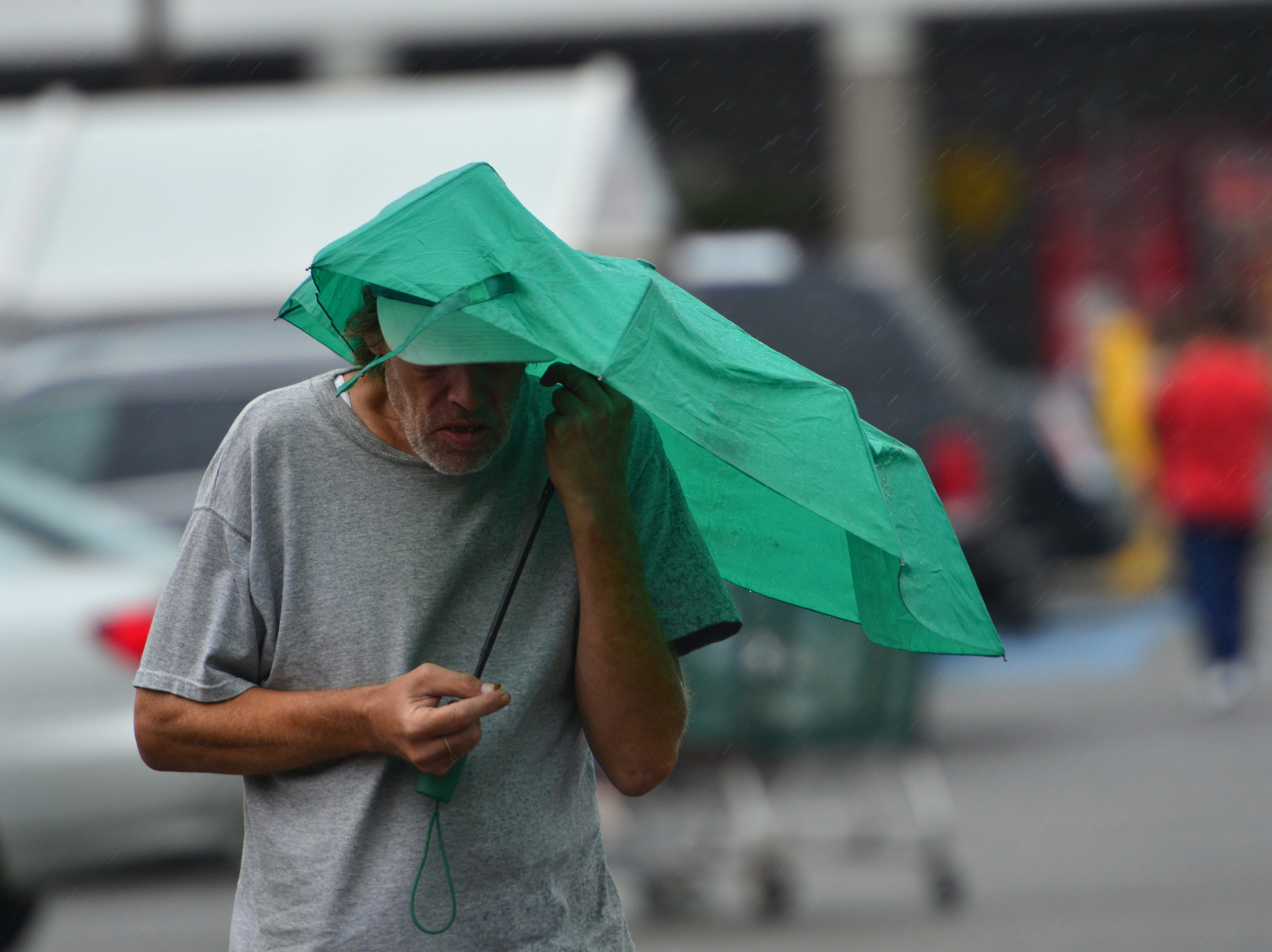 A man uses an umbrella to shield himself from the rain in Hackensack on Thursday October 11, 2018.