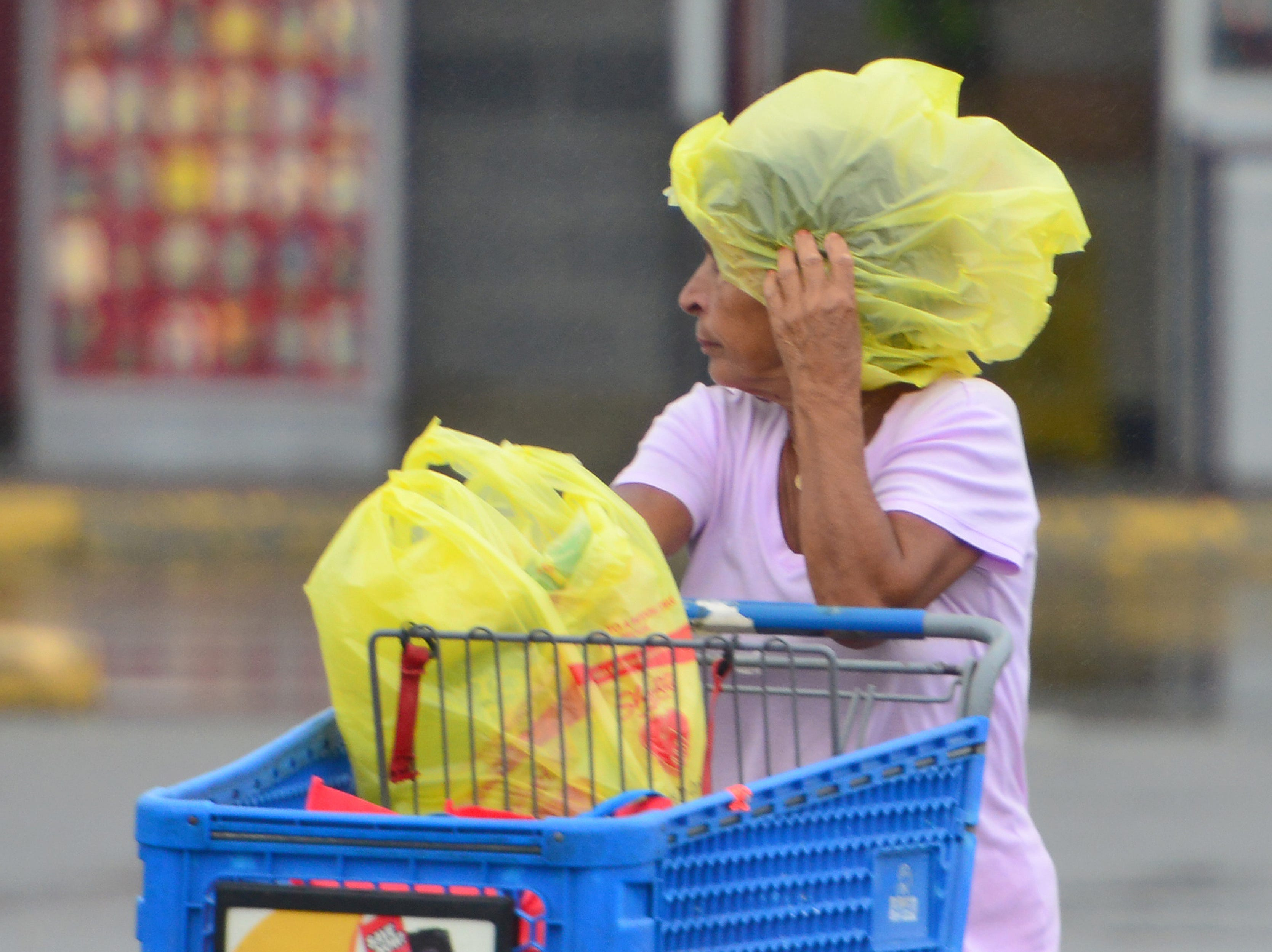 A woman uses a grocery bag to cover her head to shield herself from the rain in Hackensack on Thursday October 11, 2018.