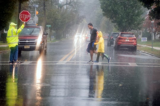 A crossing guard stops traffic on Maywood Avenue in Maywood during a downpour on Thursday, October 11, 2018.