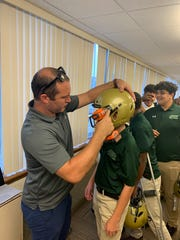 St. Joseph football players line up to have their new helmets custom-fit by Vicis representatives on Thursday.