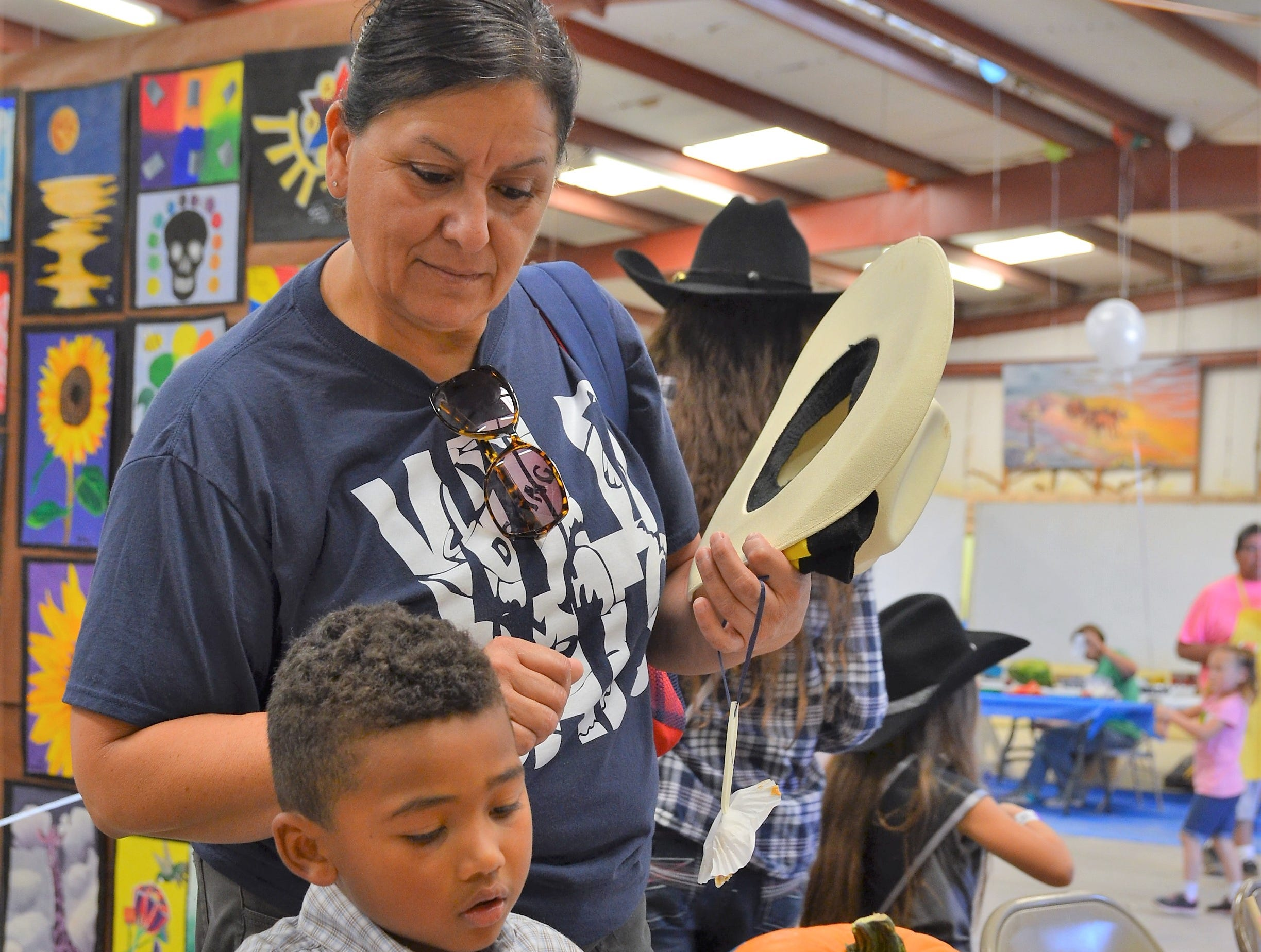 D'Kadence Dominguez, 4, paints his pumpkin, while his grandma Martha looks on.