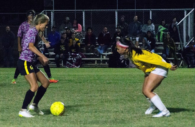During Tuesday's home conference game against the Centennial Lady Hawks, Alamogordo Lady Tiger Shawna Williams (13) shouts words of encouragement for teammate Sheyenne Drake (2) who seeks a path past Lady Hawks defender Precious Ruiz (15).