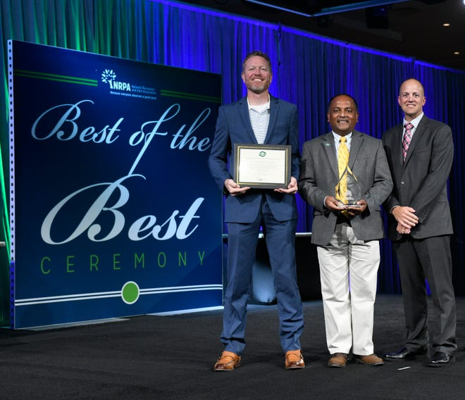 Canton Leisure Services Director Greg Hohenberger, Commission for Accreditation of Park and Recreation Agencies Chair Subhajeet Seve Ghose, and Canton Leisure Services Deputy Director Jon LaFever pose for a photo with the distinguished CAPRA Re-Accreditation Award at the 2018 NRPA Congress and Legislative Forum held in Indianapolis, Indiana.