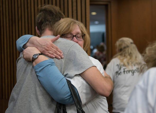 Sheryl McIntyre, mother of victim Shannon McIntyre, hugs Nick Paré Jr., the son of victim Nicholas Paré, after the sentencing of Michael Stack.