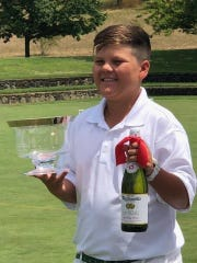 Blake Fields, an 11-year-old from Rancho Mirage, shows the trophy and sparkling cider he won at a tournament in Sonoma. The cider replaced the wine usually given to the winner.