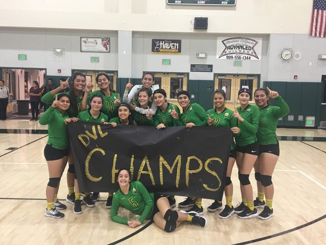 The Coachella Valley volleyball team poses with a DVL Champs sign after beating Banning on Wednesday and earning a share of the league title.