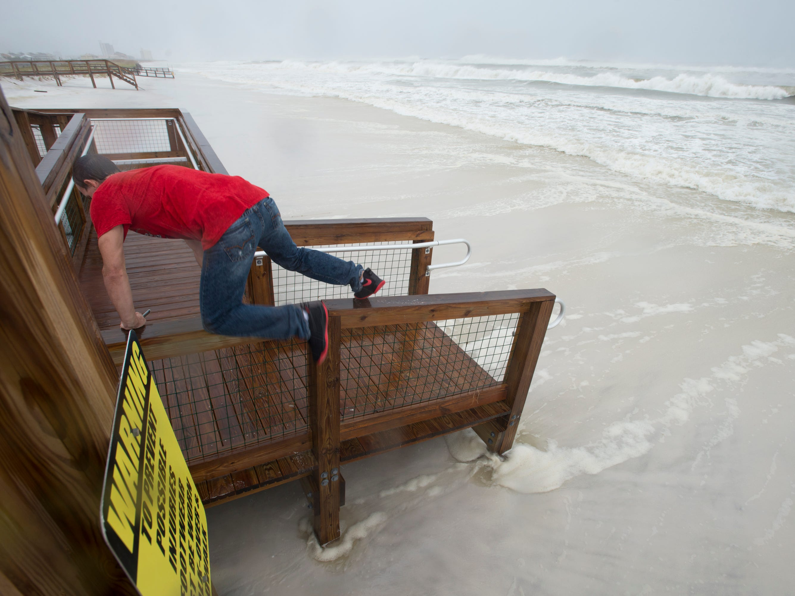 Robert Moodyham jumps on a railing as a wave gets near while taking photos of the surf as Hurricane Michael arrives in Pensacola on Wednesday, October 10, 2018.