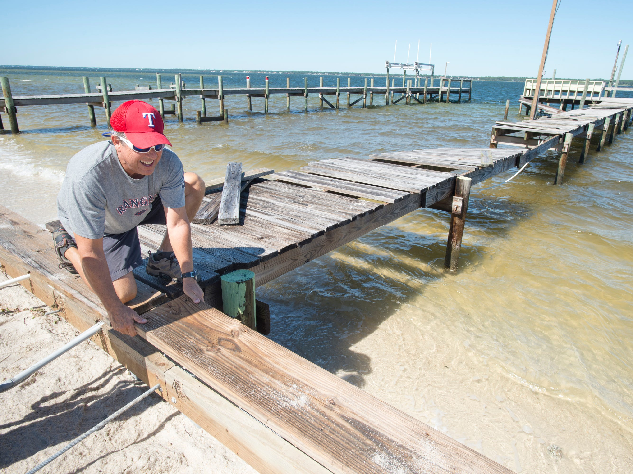 Pepe Fernandez works on repairing his dock along Grand Navarre Blvd. in Navarre on Thursday, October 11, 2018.  Fernanadez explained that he is grateful that nothing else was damaged during Hurricane Michael and that it could have been much worse.