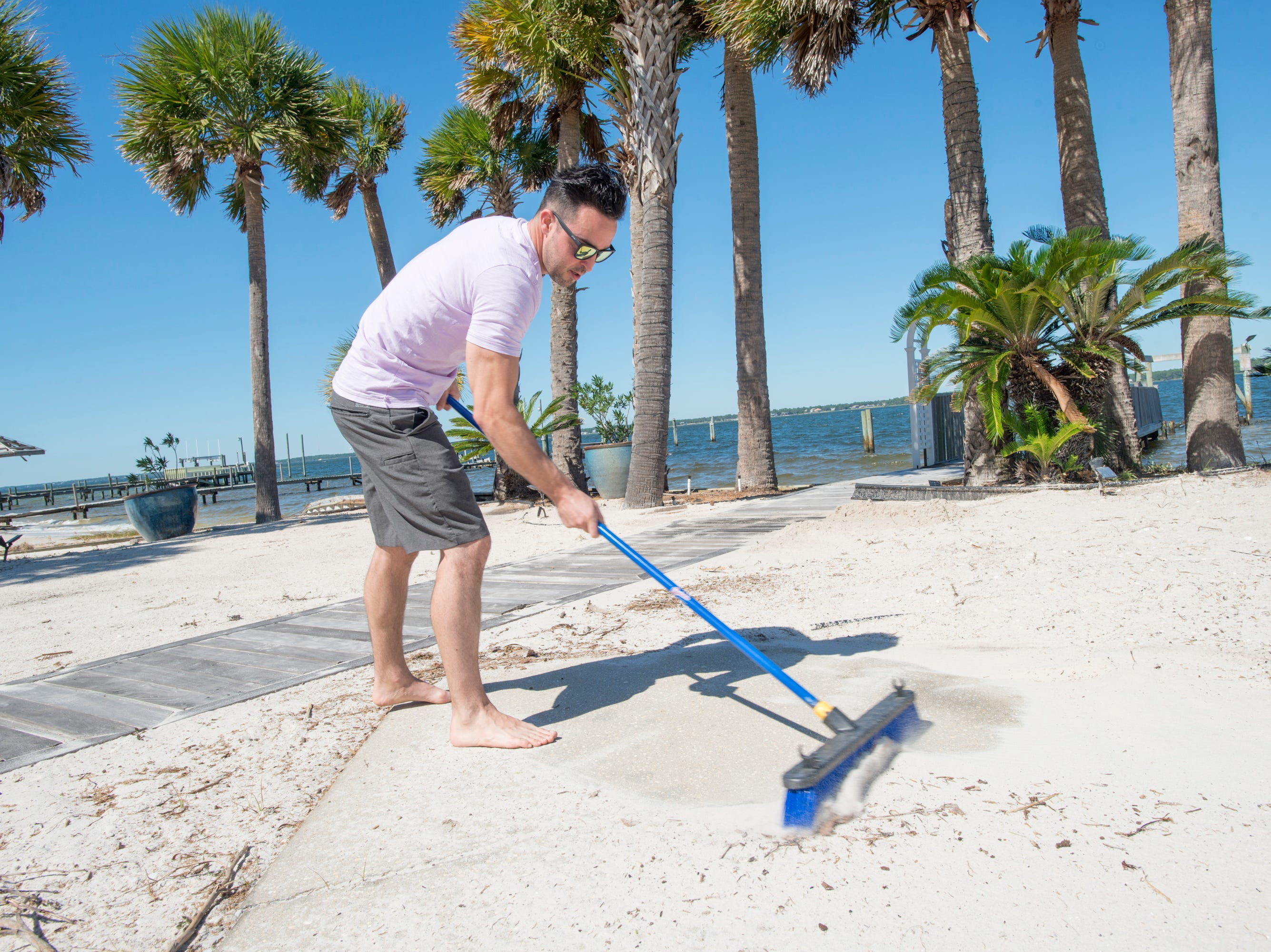 Kevin Tobin sweeps up sand after Hurricane Michael at the house that he and his fiance Danielle rented along Grand Navarre Blvd. in Navarre on Thursday, October 11, 2018.  Tobin and Danielle will be getting married on Saturday and will be having their reception on this property.  They are grateful that the only damage was to the deck and some sand that needed to be swept away.