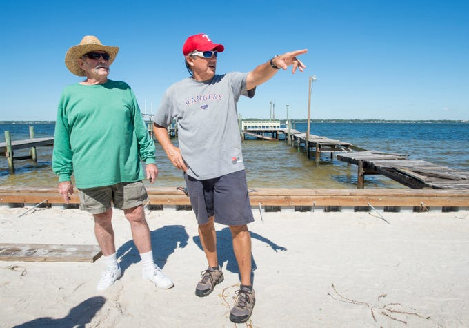 Chuck Moseley, left, listens as Pepe Fernandez talks about the damage done to his dock (as well as to two adjacent docks) during Hurricane Michael on Grand Navarre Blvd. in Navarre.  Fernanadez explained that he is grateful that nothing else was damaged.