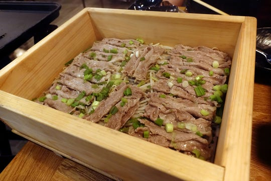 Beef cooked in a hinoki box at Jin Shabu in Chandler.