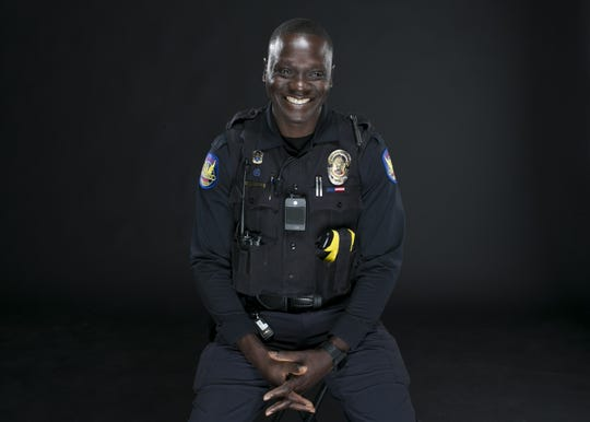 Phoenix police officer Germain Dosseh sits in the studio at the Arizona Republic in Phoenix on Wed. Sep. 12, 2018. Dosseh fled Togo, Africa to become a refugee in the United States, where he would later serve in the U.S. army in Afghanistan before coming to Phoenix and joining the police force.