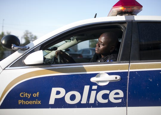 Germain Dosseh, a Phoenix police officer and Togolese refugee, sits in a patrol vehicle at the Phoenix Police Department headquarters on Wed. Aug. 15, 2018.