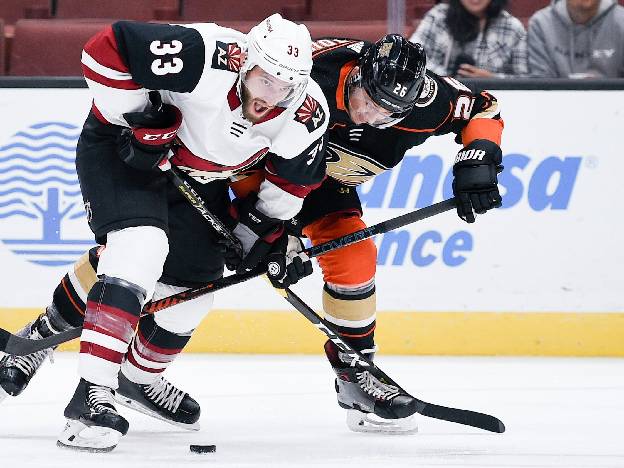 Oct 10, 2018; Anaheim, CA, USA; Anaheim Ducks defenseman Brandon Montour (26) and Arizona Coyotes defenseman Alex Goligoski (33) battle for the puck during the first period at Honda Center.